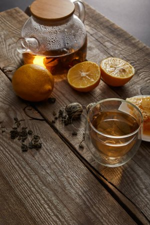 Photo for Lemons, tea balls and transparent teapot with glass of traditional chinese blooming tea on wooden surface - Royalty Free Image