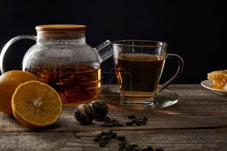 Foto de Tetera transparente y taza con té de floración tradicional sobre mesa de madera con limones aislados en negro - Imagen libre de derechos