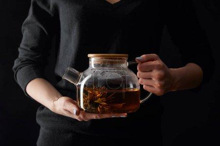Foto de Vista recortada de la mujer joven sosteniendo tetera transparente con té de flor chino aislado en negro - Imagen libre de derechos