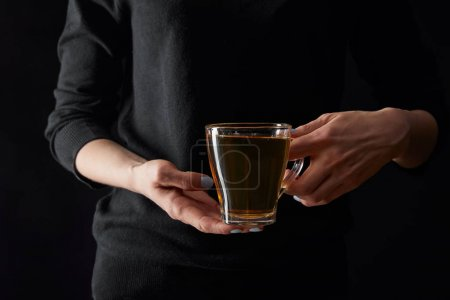Photo for Cropped view of young woman holding transparent cup of green tea isolated on black - Royalty Free Image