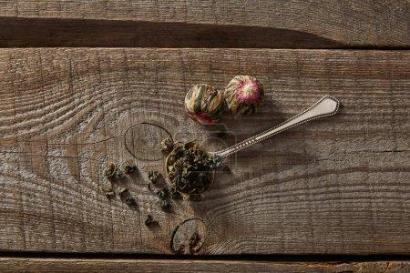Foto de Vista superior de la cuchara con té verde y bolas de té en flor en la mesa de madera - Imagen libre de derechos