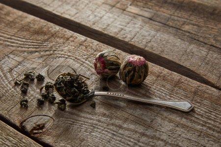 Foto de Cuchara con té verde y bolas de té en flor en la mesa de madera - Imagen libre de derechos