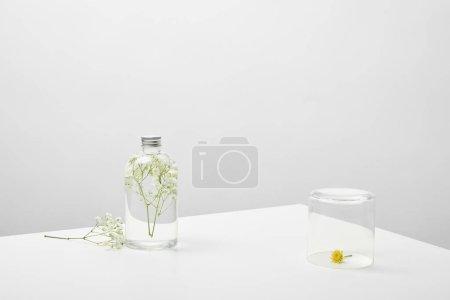 Photo pour Bouteille avec le produit normal de beauté et les fleurs sauvages blanches sur le fond gris - image libre de droit