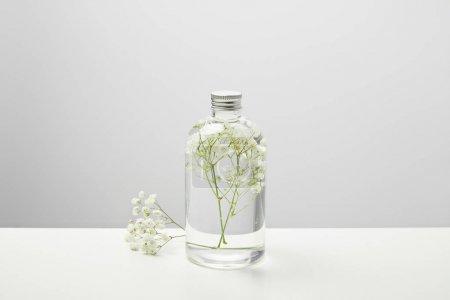 Photo pour Produit de beauté organique dans la bouteille transparente et les fleurs sauvages blanches sur le fond gris - image libre de droit