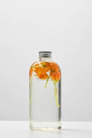 Photo pour Produit cosmétique organique dans la bouteille transparente avec des fleurs oranges sur la table blanche d'isolement sur le gris - image libre de droit