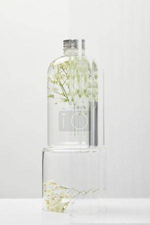 Photo pour Produit cosmétique organique dans la bouteille transparente avec des fleurs sauvages derrière le verre sur la table blanche sur le fond gris - image libre de droit