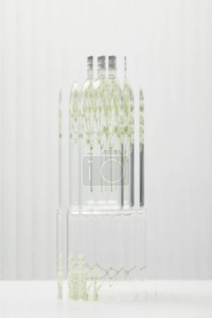 Photo for Blurred organic cosmetic product in transparent bottle with wildflowers behind glass on grey background - Royalty Free Image