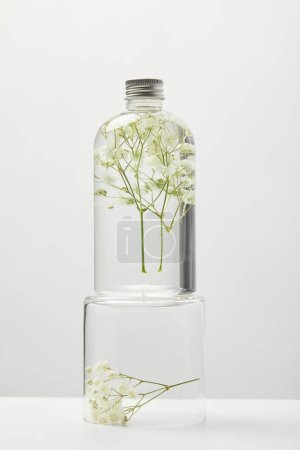 Foto de Organic cosmetic product in transparent bottle with wildflowers on stand isolated on grey - Imagen libre de derechos