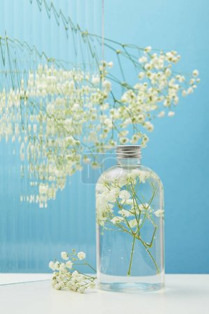 Photo for White wildflowers behind textured glass near organic beauty product in bottle on blue background - Royalty Free Image