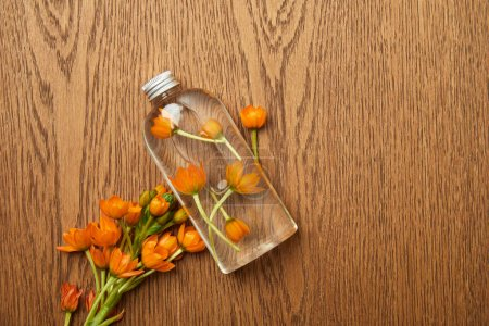 Photo for Top view of transparent bottle with organic beauty product near orange flowers on wooden background - Royalty Free Image