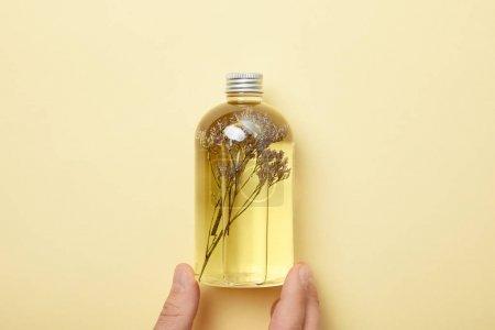 Photo pour Vue recadrée de la bouteille de fixation d'homme avec le produit normal de beauté et les herbes sur le fond jaune - image libre de droit