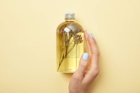 Photo for Cropped view of woman holding bottle with natural beauty product and herbs on yellow background - Royalty Free Image