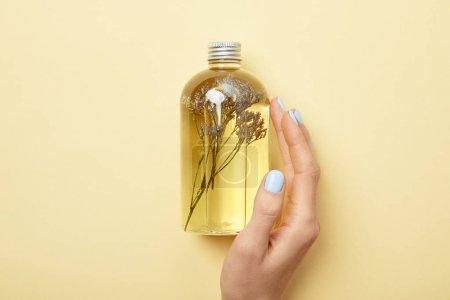 Photo pour Vue recadrée de la bouteille de fixation de femme avec le produit normal de beauté et les herbes sur le fond jaune - image libre de droit