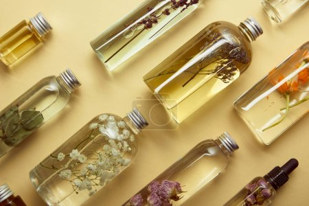 Photo pour Top view of bottles with organic beauty products and dried wildflowers on yellow background - image libre de droit