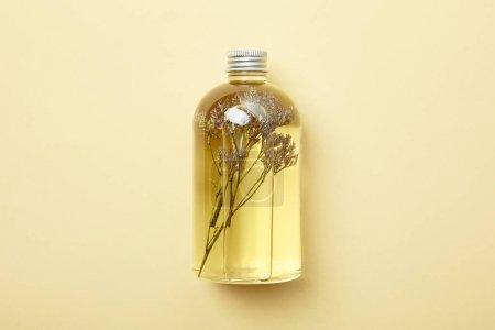 Photo pour Vue supérieure de la bouteille avec le produit de beauté organique et les fleurs sauvages séchées sur le fond jaune - image libre de droit