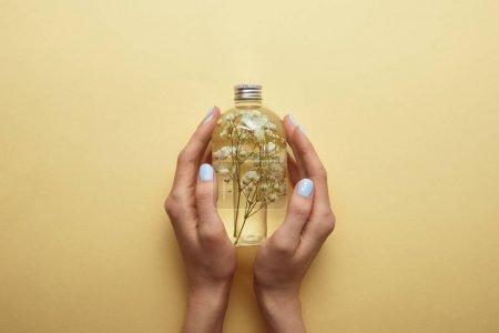 Photo pour Vue partielle de la bouteille de fixation de femme avec le produit normal de beauté et les herbes dans des mains sur le fond jaune - image libre de droit
