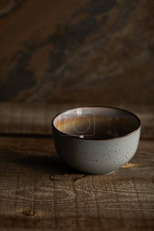 Photo for Ceramic bowl on rustic wooden table with copy space - Royalty Free Image