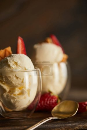 Photo for Close up of delicious ice cream with strawberry in glass and spoon - Royalty Free Image