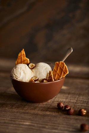 Photo for Delicious ice cream scoops with pieces of waffle and hazelnuts in bowl on wooden table - Royalty Free Image