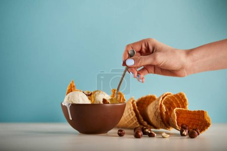 Photo for Partial view of woman with spoon, bowl of ice cream, hazelnuts and waffle cones on blue - Royalty Free Image