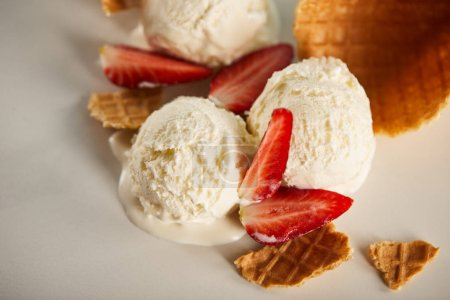 Photo for Close up view of waffle pieces and delicious melting ice cream with strawberries on grey - Royalty Free Image