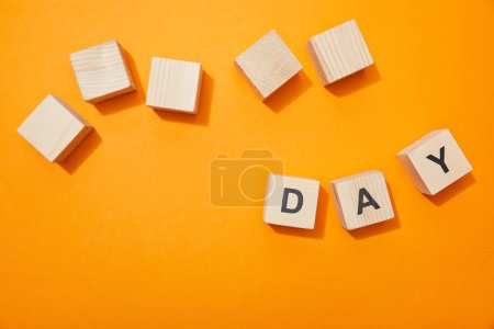 Photo for Top view of wooden blocks with letters on orange surface - Royalty Free Image