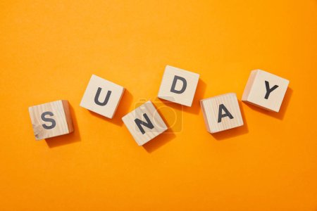 Foto de Top view of wooden blocks with letters on orange surface - Imagen libre de derechos