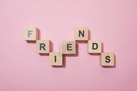 Photo pour Vue de dessus des cubes en bois avec des lettres sur la surface rose - image libre de droit