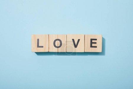 Photo pour Vue supérieure des cubes en bois avec des lettres sur la surface bleue - image libre de droit