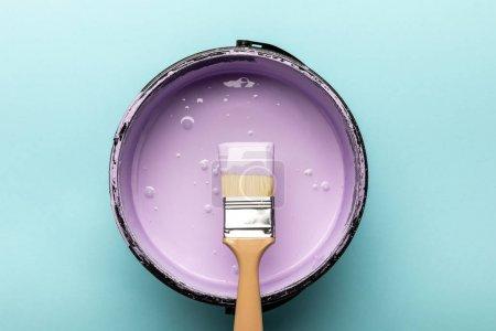 Photo pour Vue du dessus du seau avec peinture violette et pinceau sur bleu - image libre de droit