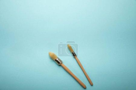 Photo pour Vue de dessus de deux brosses sur la surface bleue - image libre de droit