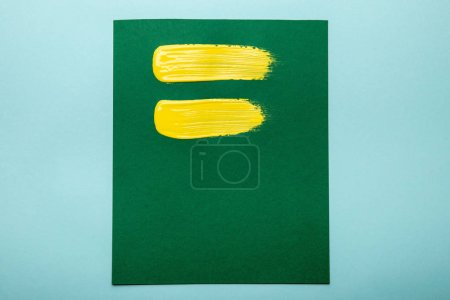Photo for Top view of green canvas with yellow brushstrokes isolated on blue - Royalty Free Image
