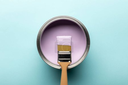 Photo for Top view of tin with purple paint and brush on blue surface - Royalty Free Image