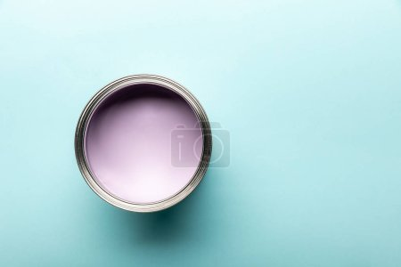 top view of tin with purple paint on blue surface