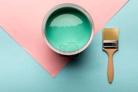 Photo pour Vue supérieure de l'étain avec la peinture verte et le pinceau sur la surface bleue et rose - image libre de droit
