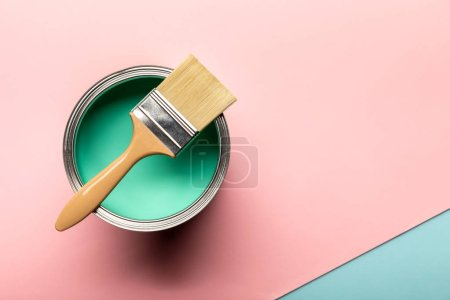 Photo for Top view of tin of green paint and brush on pink surface - Royalty Free Image