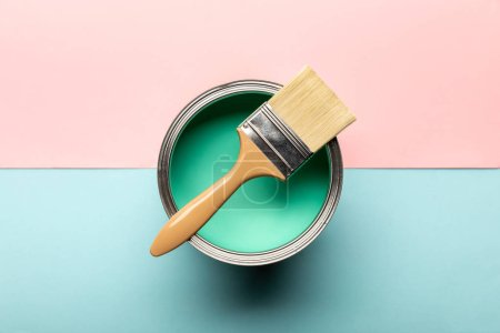 Photo for Top view of can on green paint and brush on pink and blue surface - Royalty Free Image