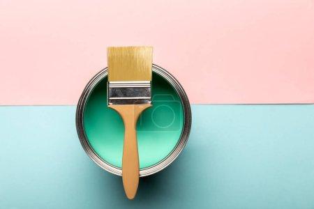 vue du dessus de l'étain sur peinture verte et pinceau sur surface rose et bleue