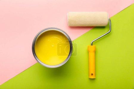 Photo pour Vue supérieure de l'étain avec la peinture jaune et le rouleau de peinture sur la surface rose et verte - image libre de droit