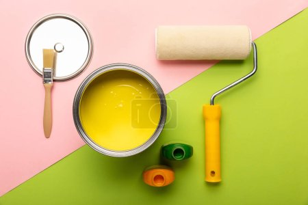 Photo for Top view of tin with yellow paint, bottles, brush and paint roller on pink and green surface - Royalty Free Image