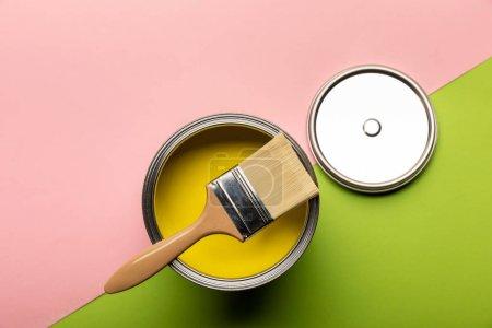 Photo pour Vue supérieure de l'étain avec la peinture et le pinceau jaunes sur la surface rose et verte - image libre de droit