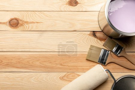 Photo for Top view of brushes, tin of purple paint and paint roller on wooden surface - Royalty Free Image