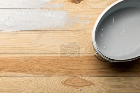 Photo for Top view of bucket with white paint on wooden surface - Royalty Free Image