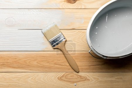 Photo for Top view of brush and bucket of white paint on wooden surface - Royalty Free Image