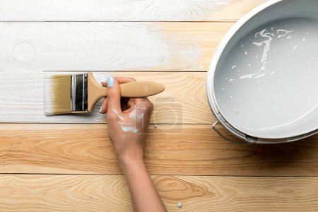 Photo for Cropped view of woman painting wooden surface in white - Royalty Free Image