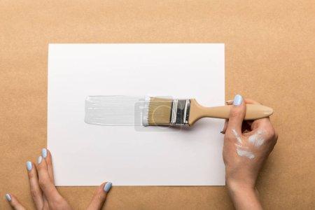 Photo pour Vue partielle de la peinture de femme avec le pinceau sur le papier - image libre de droit