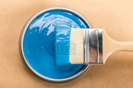 Photo for Top view of tin with blue paint and brush on brown - Royalty Free Image
