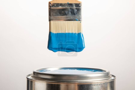 Photo for Tin with blue paint and brush on white - Royalty Free Image