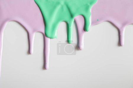 Foto de Fondo blanco con pinturas de flujo púrpura y verde - Imagen libre de derechos