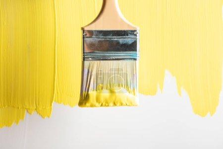 Photo pour Vue de dessus du pinceau sur la surface jaune peinte - image libre de droit